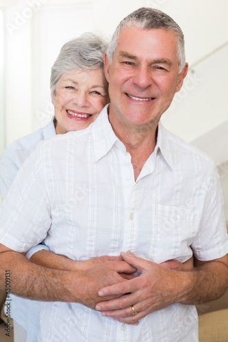 Retired couple smiling at camera and hugging