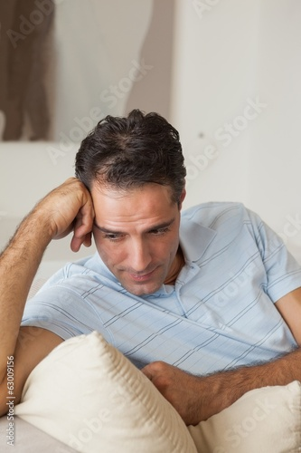 Close-up of a thoughtful man sitting on sofa
