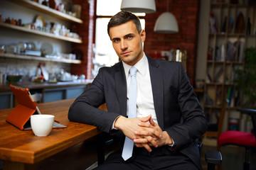 Confident businessman in formal cloths drinking