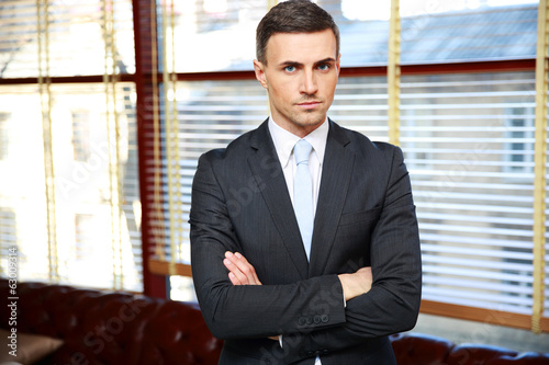 Confident businessman with arms folded in office