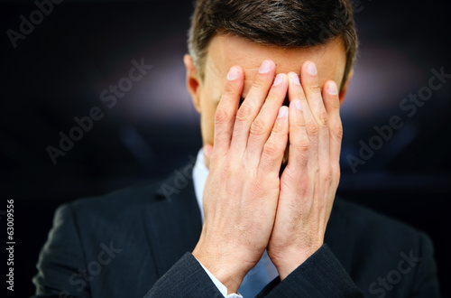 Frustrated businessman with hands on face