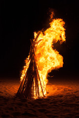 A pyre burning in the night on a beach during summer holidays.