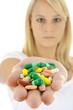 Frau mit Hand voller Tabletten und Pillen