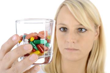 Frau hält Glas voller Pillen und Tabletten