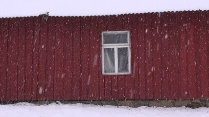 winter  snow falling and  farm house wall with window