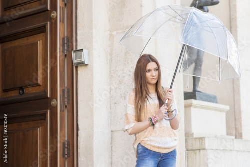Attractive young woman with umbrrella leaving her house.