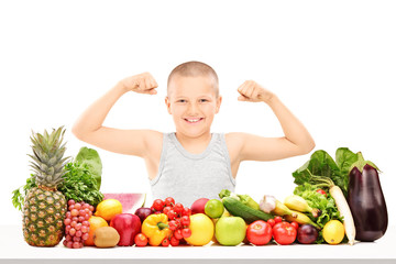 Boy showing muscles behind pile of vegetables