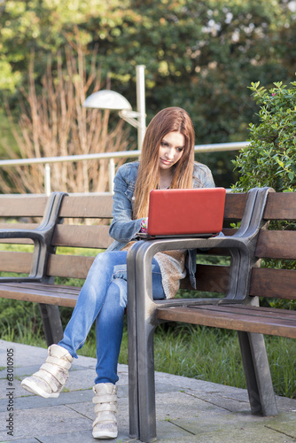 Student laptop computer and sitting on bench in the park.