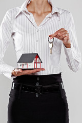 Female holding a model house and keys isolated on grey