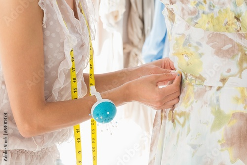Mid section of a fashion designer working on dress