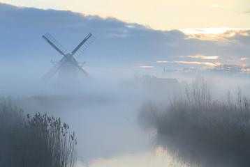 Foggy dawn at a windmill