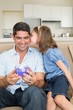 Girl kissing father holding gift box on sofa