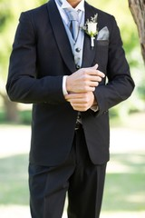Sophisticated groom adjusting sleeve in garden