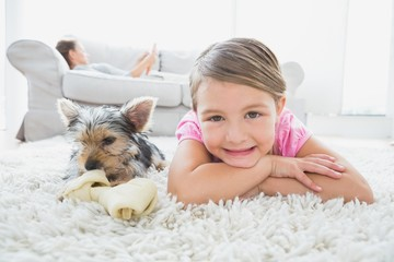 Little girl lying on rug with yorkshire terrier smiling at