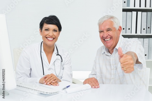 Happy senior patient gesturing thumbs up with doctor