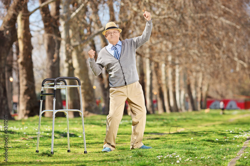 Old man with walker gesturing happiness outdoors
