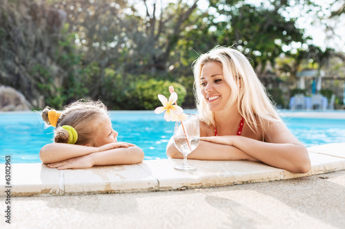 Little girl and her mother with cocktail in tropical beach pool