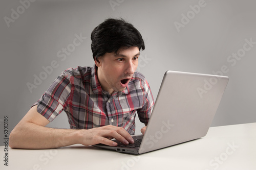 shocking man reading message on laptop computer