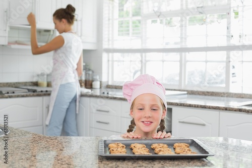 Girl looking at freshly prepared cookies with mother in kitchen