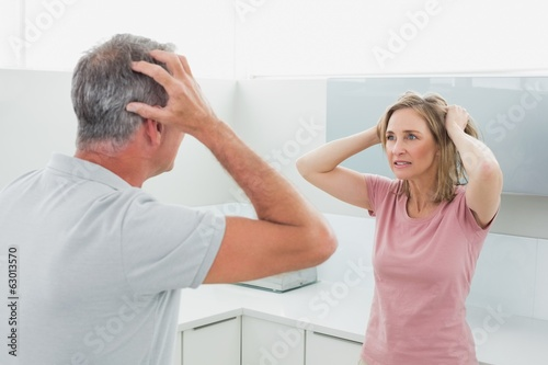Unhappy couple having an argument in kitchen