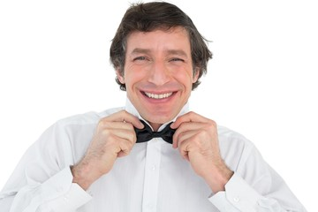Portrait of groom adjusting bow tie