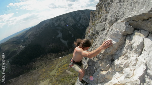 Rock climber high up on limestone cliff Turzii Gorge
