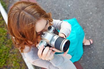 Young woman uses digital slr photocamera.