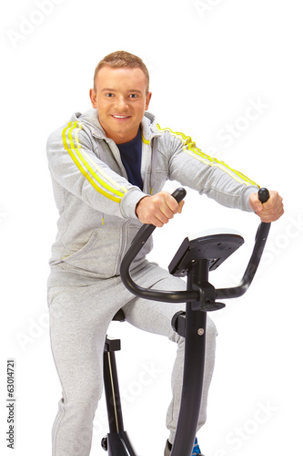 Young man uses stationary bicycle trainer.