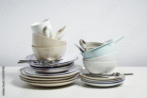 Dirty dishes pile needing washing up on white background - 63014748