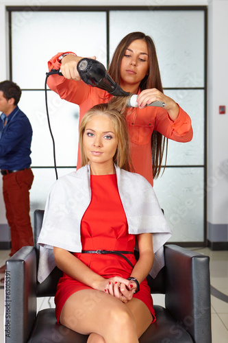 Barbershop. Woman haircut. Use of hair dryer.