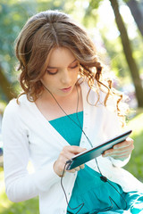 Young woman listens music using tablet pc.