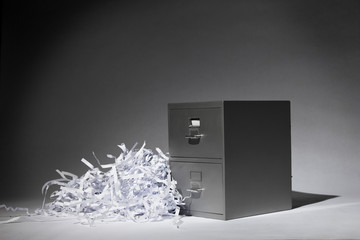 A grey filing cabinet in a spotlight.