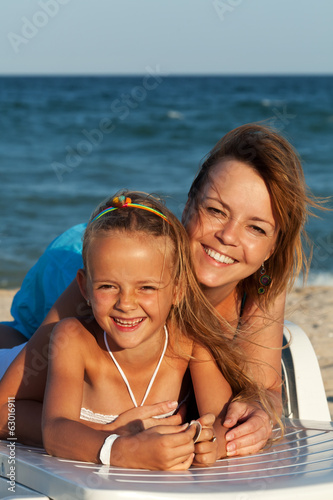 Happy woman and little girl at the sea side