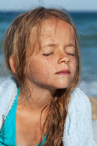 Little girl soaking up the sun on the windy sea shore