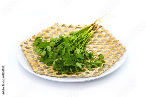 Coriander Coriandrum sativum on wickerwork dish white background