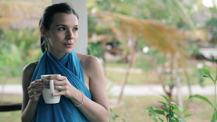 Sad, pensive beautiful woman drinking coffee on house patio