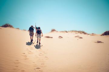 hikers climbing sand dunes