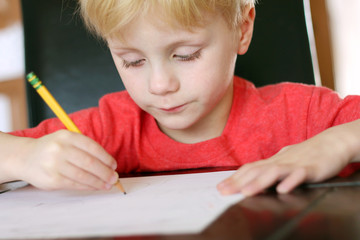 Young Child Focusing on Work as he Writes with Pencil