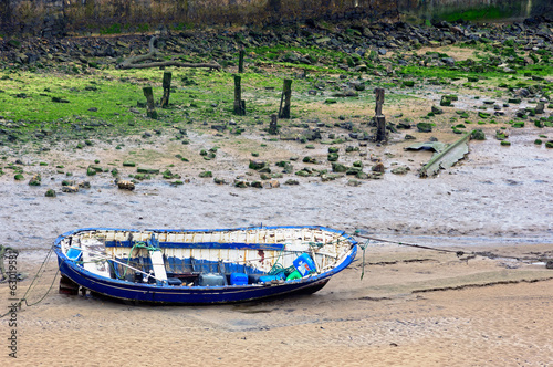 wooden boat stranded on sand due low tide