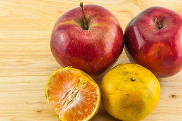 Apple & tangerine on wood background