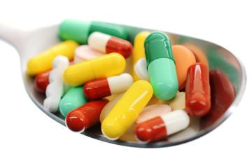 Bunte Tabletten und Pillen auf Löffel