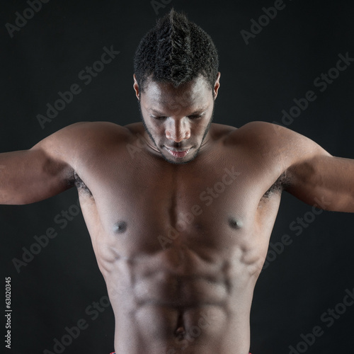 Strong young man shirtless portrait against black background.
