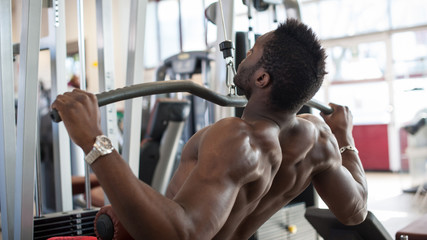 Strong young black man exercising at the gym.