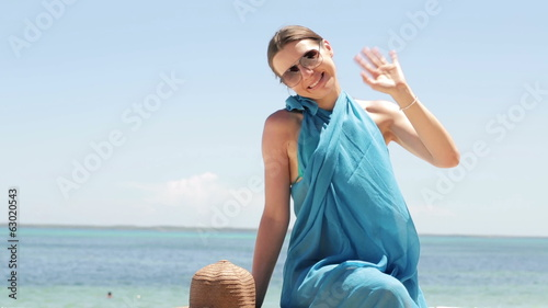 Sexy woman waving hand to camera by the sea
