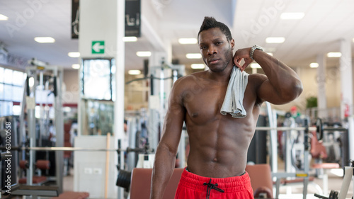 Strong black man having a pause in the gym.
