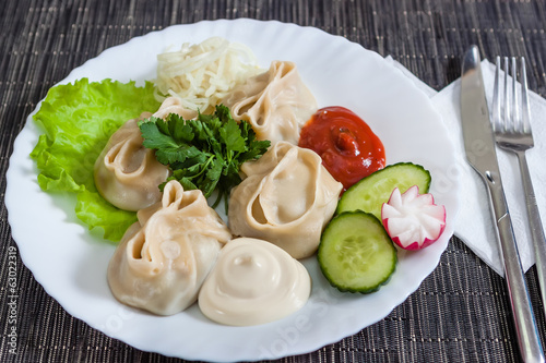 Meat dumplings with lettuce, cucumbers and radishes and greens
