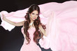 Beautiful brunette girl wearing in pink dress isolated on black