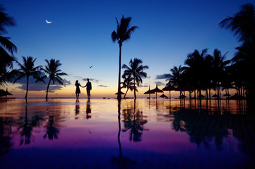 Silhouettes of young couple at scenic sunset