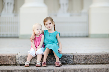 Portrait of two little sisters outdoors