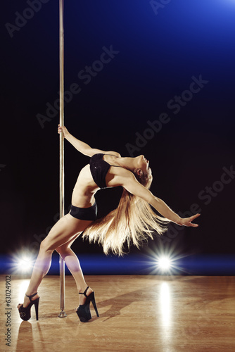 Young sexy pole dance woman with fluttering hair on stage